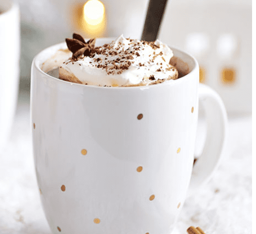 Butterscotch Schnapps Hot Chocolate in white mug with gold polka dots with cinnamon garnish